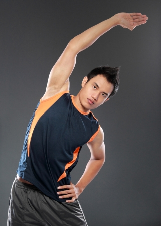 young fitness man making stretching exercises seen from behind photo