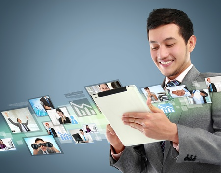 potrait of successful young business man with tablet in the office photo