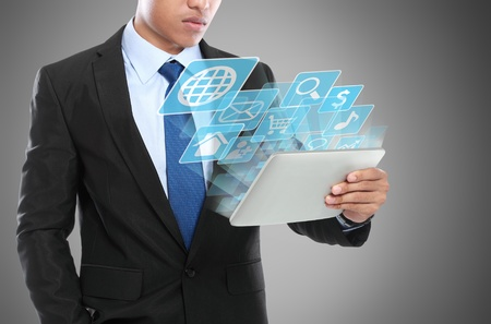 Business man using tablet PC and smiling with conceptual image photo