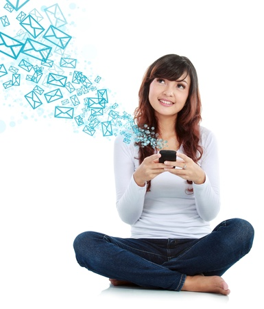 Woman sitting on floor and text messaging on a mobile phone isolated over white background photo