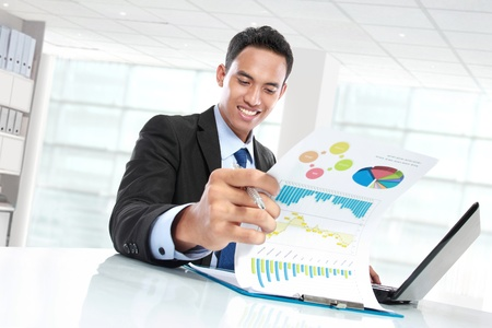 potrait of successful businessman showing growth chart and smiling photo