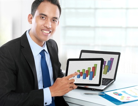 Business man showing tablet pc with success growth graph on screen photo