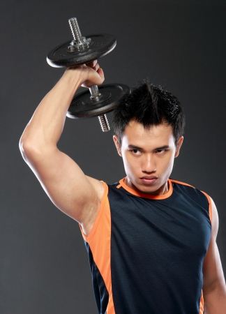 Handsome young man lifting weight photo