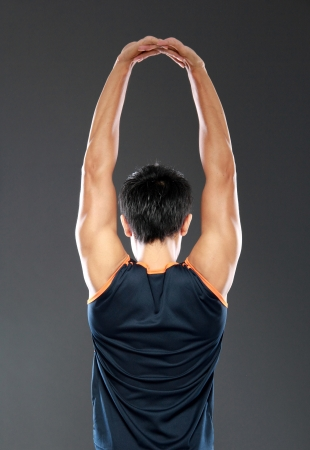 stretches: young fitness man making stretching exercises seen from behind Stock Photo