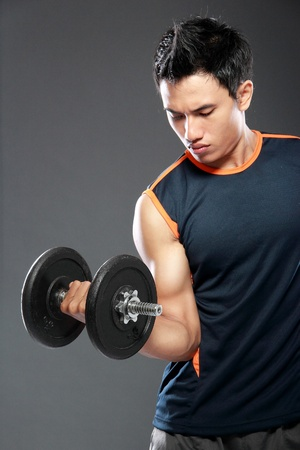 Young man is exercising with barbell in gym to strengthen the muscles photo