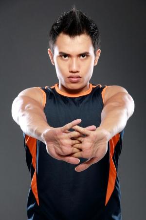 young sport fitness man making stretching exercises  ang looking at camera photo