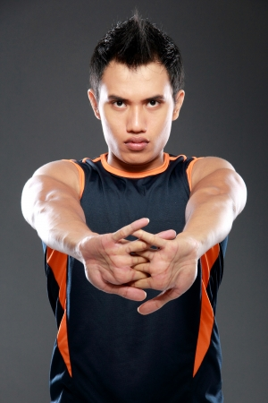 Men exercise: young sport fitness man making stretching exercises ang looking at camera