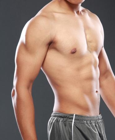 hombre sin camisa: un modelo masculino joven y sexy posando sus músculos