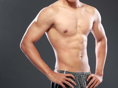 asian abs: a young and fit male model posing his muscles