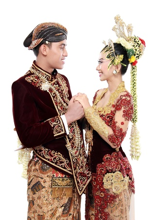 Traditional java wedding couple husband and wife hold each other isolated over white background photo