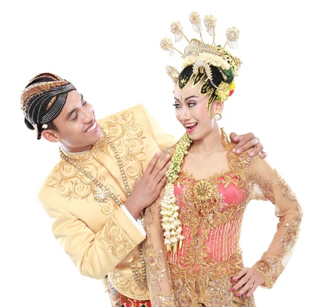 happy traditional java wedding couple husband and wife embrace each other isolated over white background photo