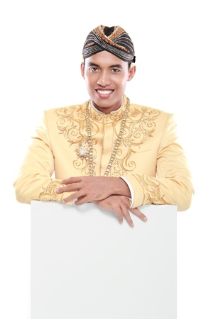 man wearing traditional dress of java holding blank board isolated on white background photo