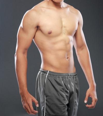 彼の筋肉ポーズ若いとフィットの男性モデル 写真素材
