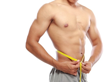 portrait of Men with perfect abs measuring his waist photo