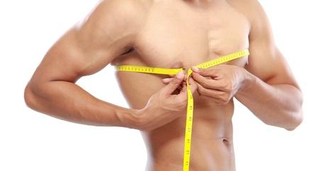 abdominal fitness: Retrato de los hombres con abdominales perfectos que mide su pecho