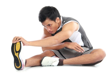 young fitness man sitting and making stretching exercises photo
