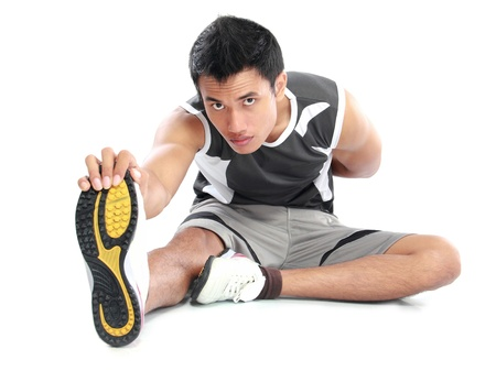 full strenght: young fitness man sitting and making stretching exercises