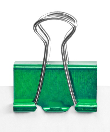 Close up of a green binder clip attached to sheet of paper photo