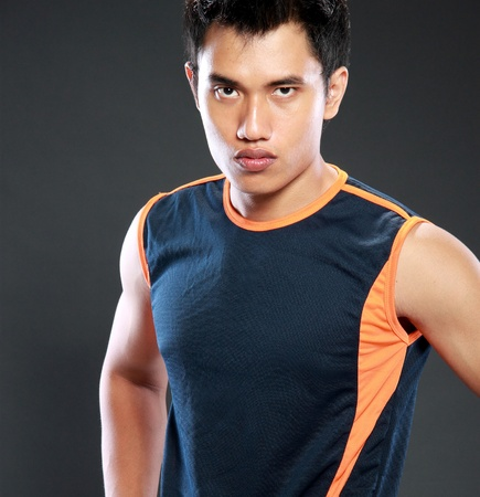 muscled: portrait of sexy male model with hands on hips and looking at camera, use blue shirt