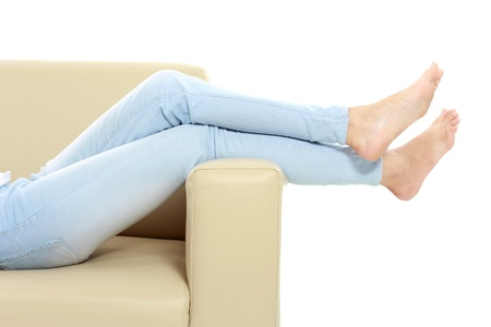 lying on couch: Young woman putting her feet up on sofa Stock Photo