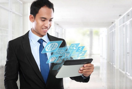 Asian Business man using tablet PC and smiling with conceptual image Stock Photo - 20599533