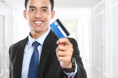 business man holding a credit card and smile on white background photo