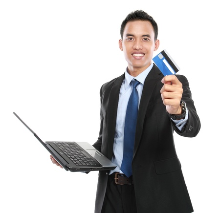 holding close: business man holding a credit card and laptop on white background