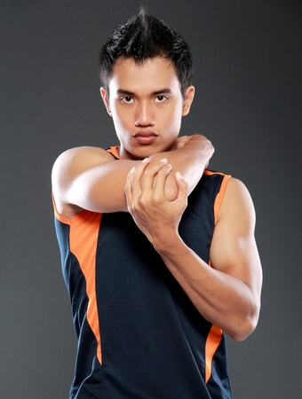 young fitness man making stretching exercises and looking at camera photo