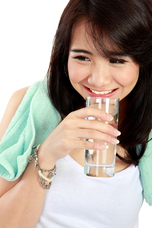 Portrait of confident young woman in sportswear holding a glass of water photo