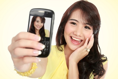 Happy young girl take the picture her self with handphone photo