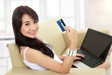 portrait of busy young woman sitting in sofa using a laptop and hold the credit card photo