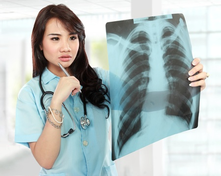 asian medical: Young asian female doctor looking at the x-ray picture of lungs