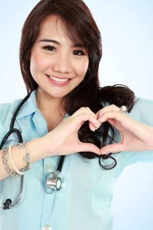 portrait of happy young nurse with heart shape hands photo