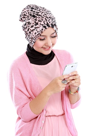 Portrait of beautiful muslim woman texting with her smartphone isolated over white background
