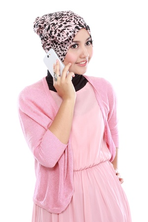 Portrait of a successful asian muslim woman talking on the cell phone and looking at camera photo