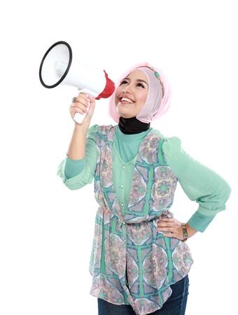 白い背景の上に孤立したメガホンを使用して叫ぶ若い魅力的なイスラム教徒の女性