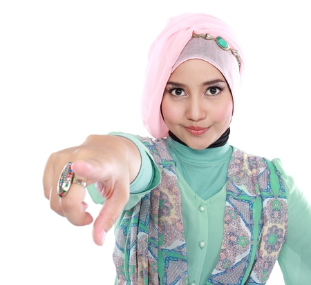 Beautiful young muslim woman pointing at the camera isolated over white background photo