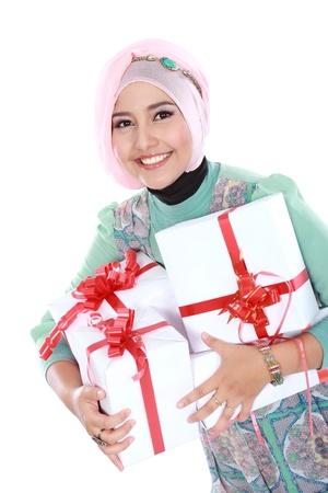 Gelukkige jonge moslim vrouw met geschenkdozen geïsoleerd over witte achtergrond Stockfoto