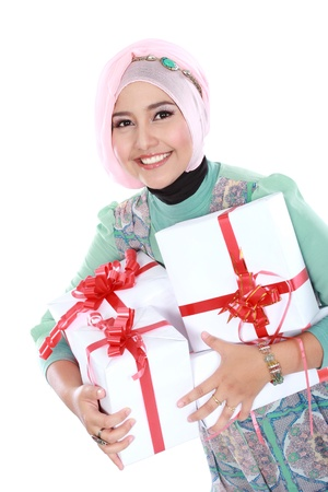 Happy young muslim woman with gift boxes isolated over white background photo