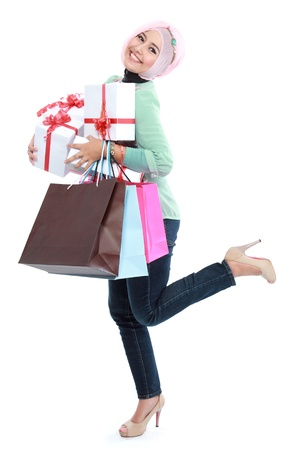 Happy of standing young woman with shopping bag and gift boxes isolated over white background photo