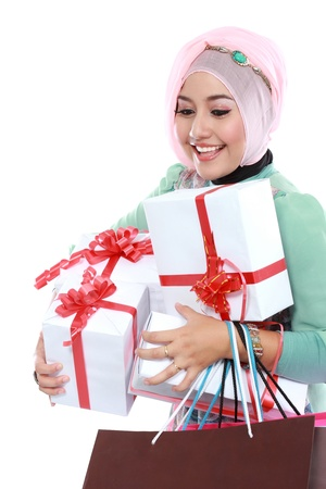 Happy young muslim woman with shopping bag and gift boxes isolated over white background photo