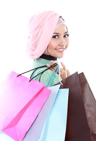 Closed up of beautiful muslim woman, in a holding in her hands a few shopping bags photo