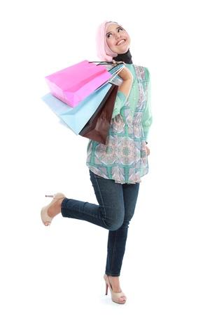 Happy of standing muslim woman with shopping bag isolated over white background photo
