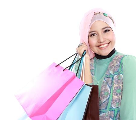 幸せな若いイスラム教徒の女性の白い背景に分離されたショッピング バッグをクローズ アップ