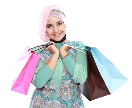 Woman in head scraf holding a few shopping bags and looking at camera