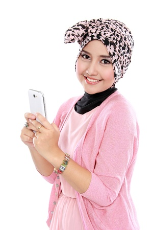 Portrait of a smiling beautiful muslim woman holding smartphone and looking at camera Stock Photo
