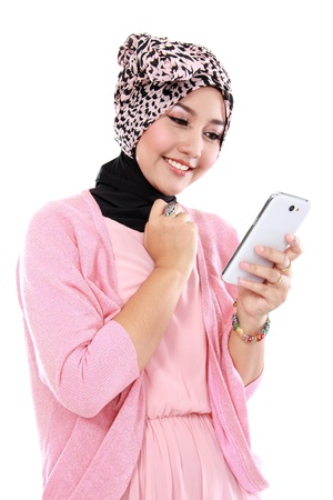 Portrait of a smiling beautiful muslim woman texting with her smartphone isolated over white background photo