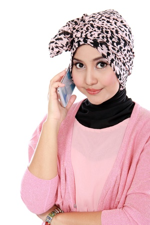 Portrait of a asian muslim woman talking on the cell phone isolated over white background photo