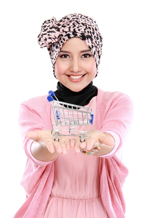 Attractive asian muslim woman with shopping cart and looking at camera photo