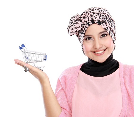Attractive asian muslim woman with shopping cart isolated on white background photo
